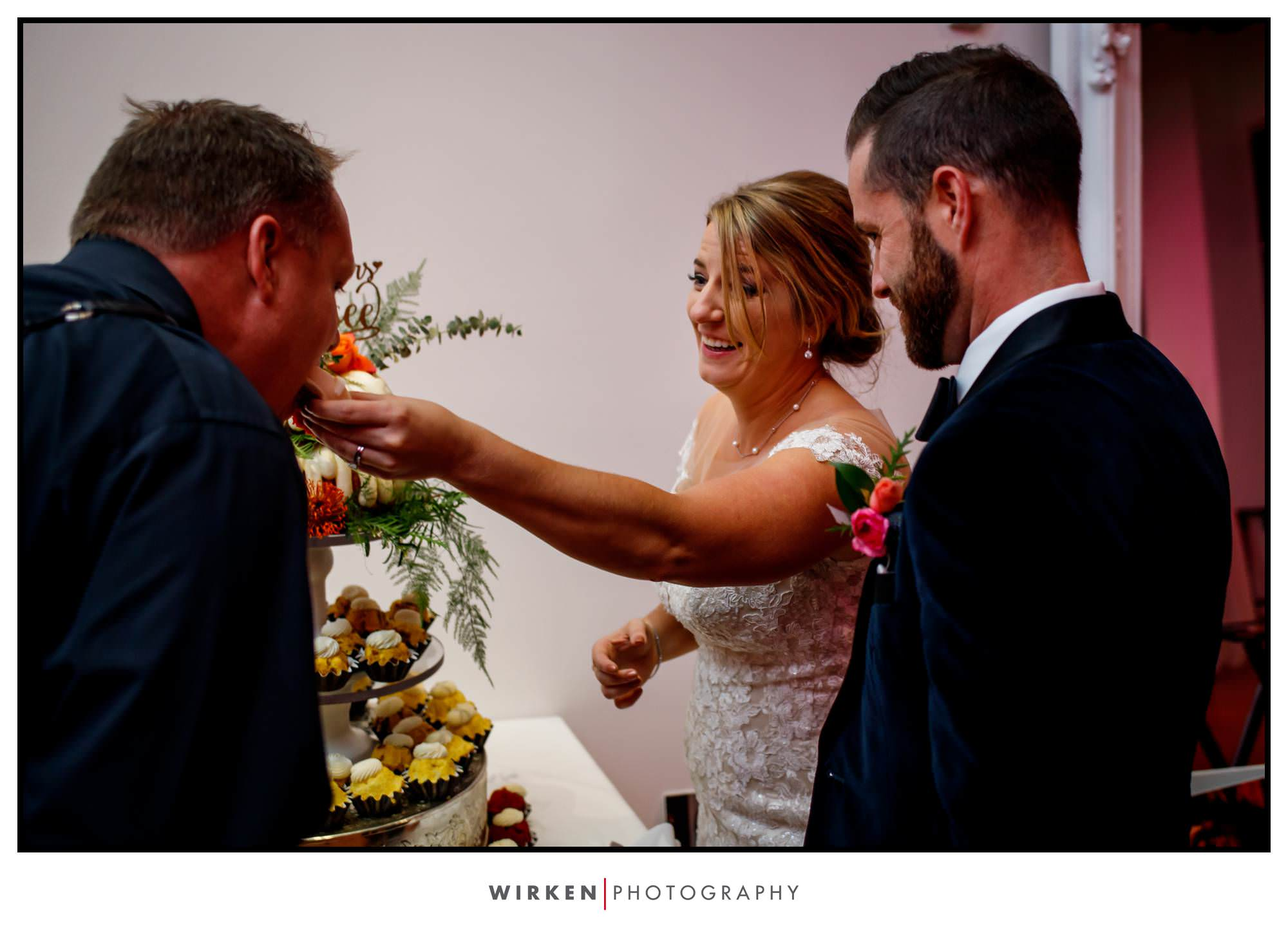 Leah feeds Kansas City wedding photographer Tyler Wirken a piece of wedding cake.