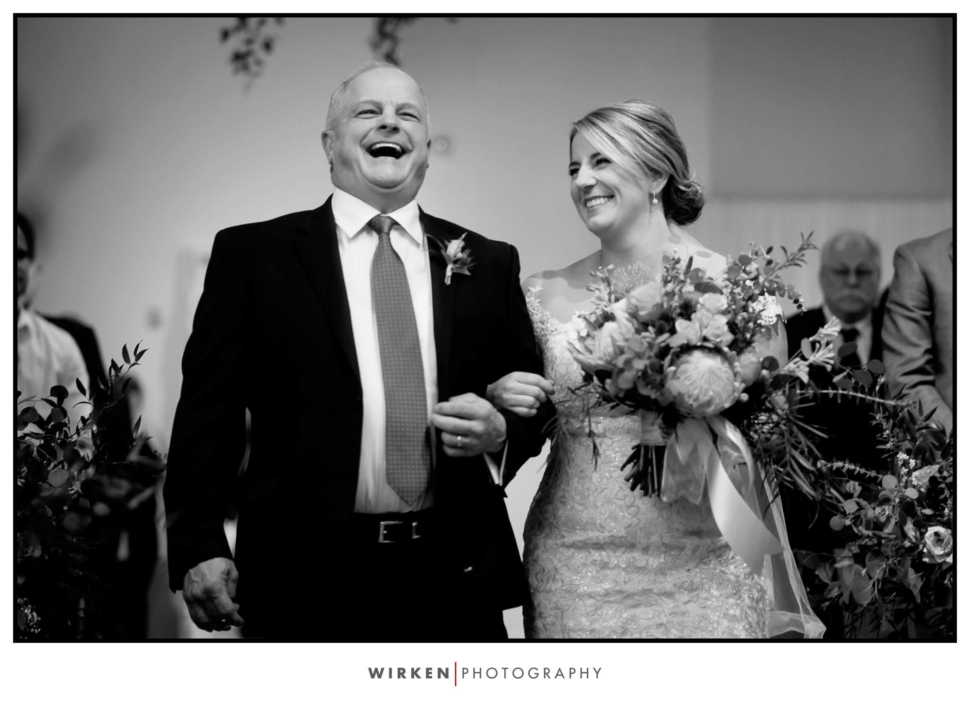 Leah's dad laughs as he walks his daughter down the aisle.