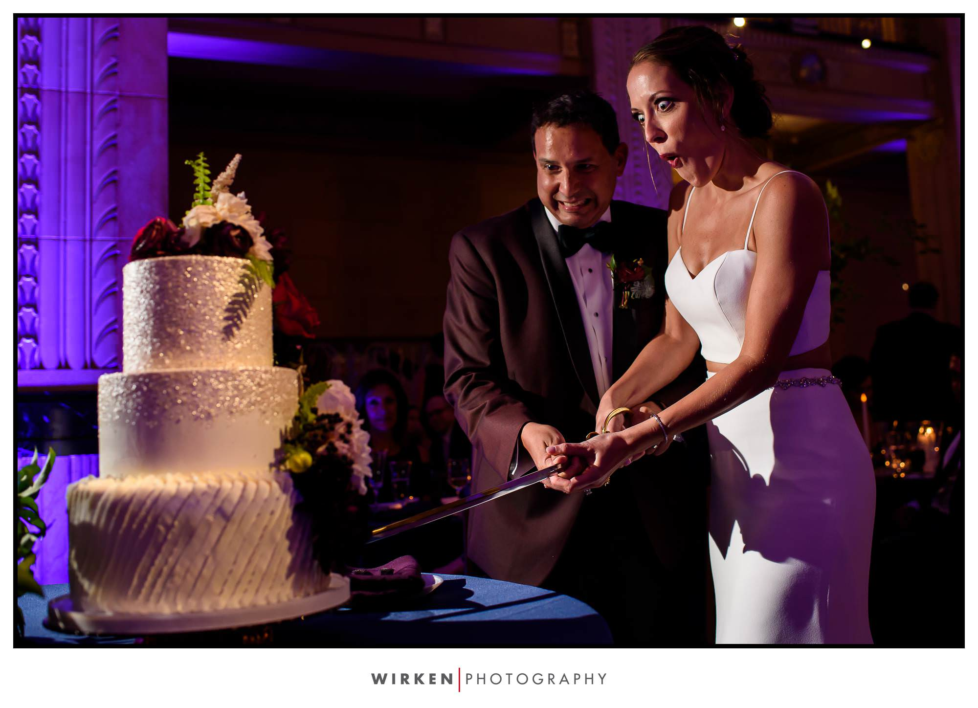 Bride and groom cut their wedding cake with a sword at the Grand Hall wedding reception in Kansas City.