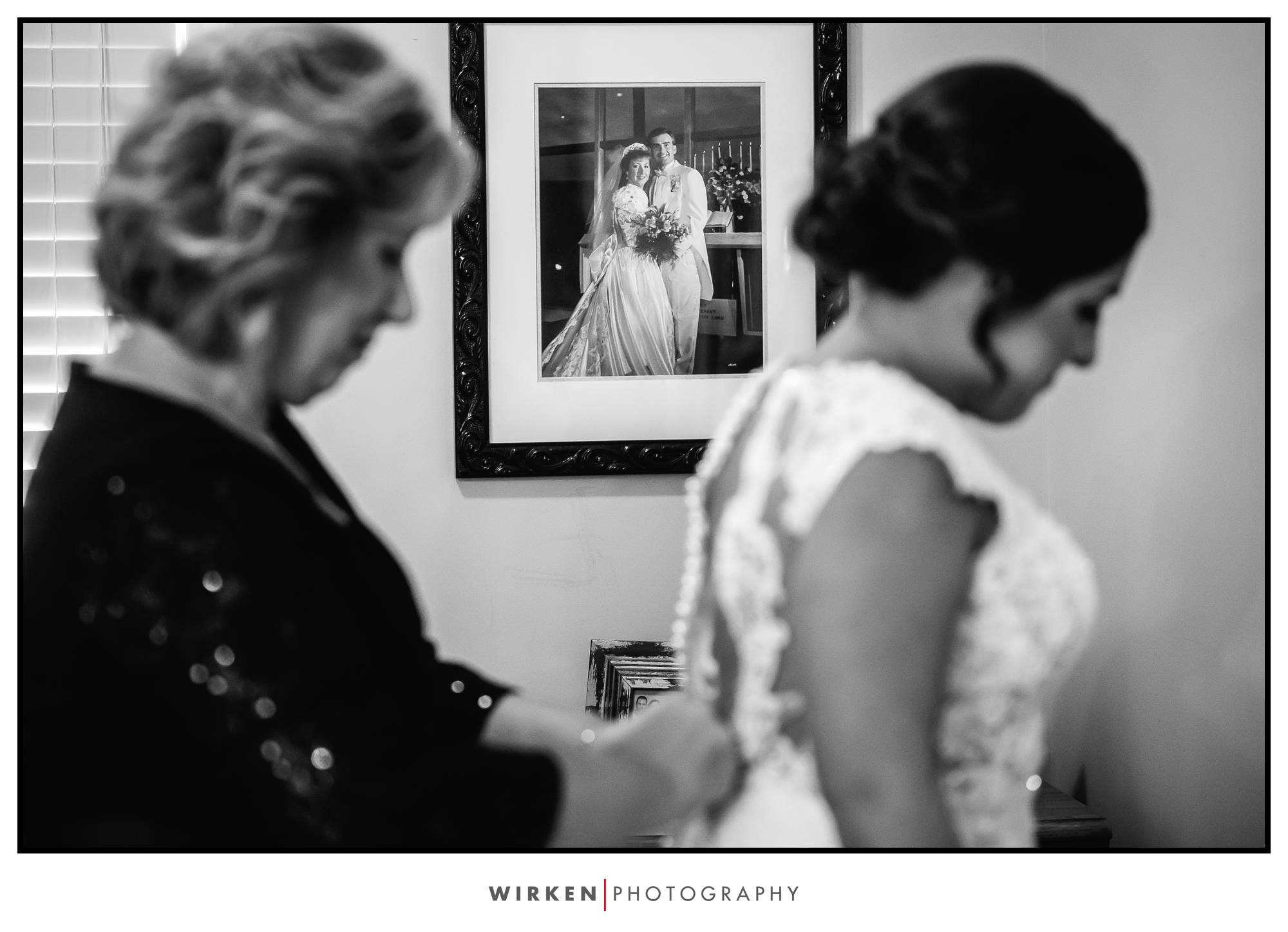 Bride gets into dress with view of parents wedding photo in this kansas city wedding